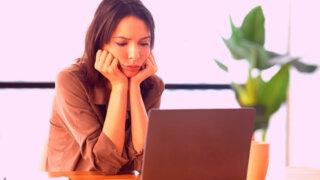 パソコンを見てイライラする女性